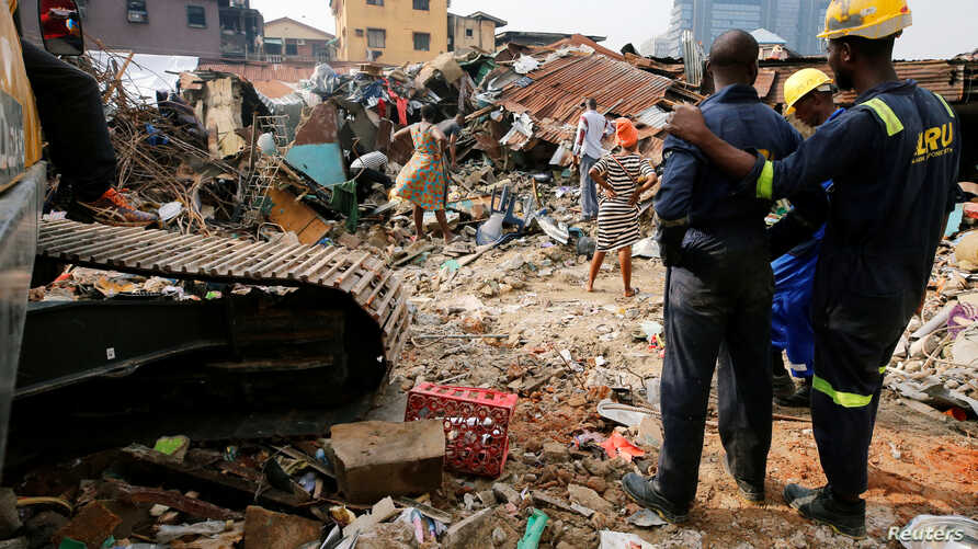 Rescuers are seen as people search for belongings at the site of a collapsed building in Nigeria's commercial capital of Lagos, Nigeria, March 14, 2019.