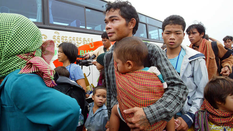 FILE -- Montagnard hill tribe members board bus after arriving at Phnom Penh International airport, July 28, 2004.