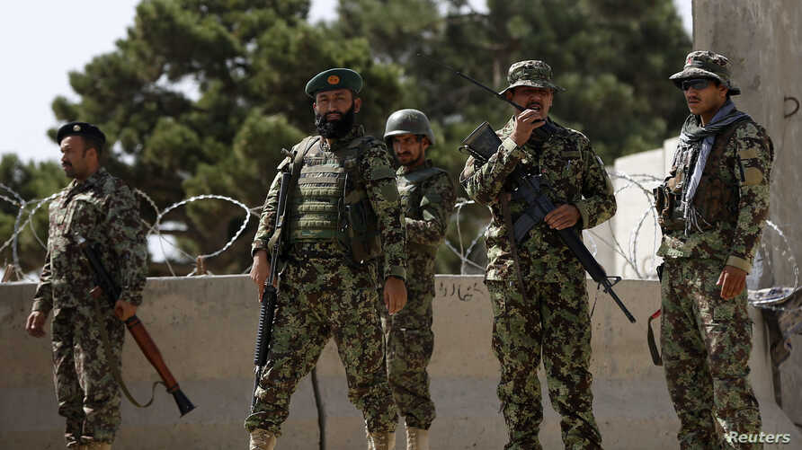 Afghan National Army (ANA) soldiers keep watch at the gate of a British-run military training academy Camp Qargha, in Kabul, Aug. 5, 2014.