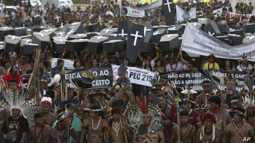 FILE - Indigenous protesters from various ethnic groups carry fake coffins representing indians killed over the demarcation of land, as they demand the demarcation of indigenous lands, outside the National Congress in Brasilia, Brazil, April 25, 2017