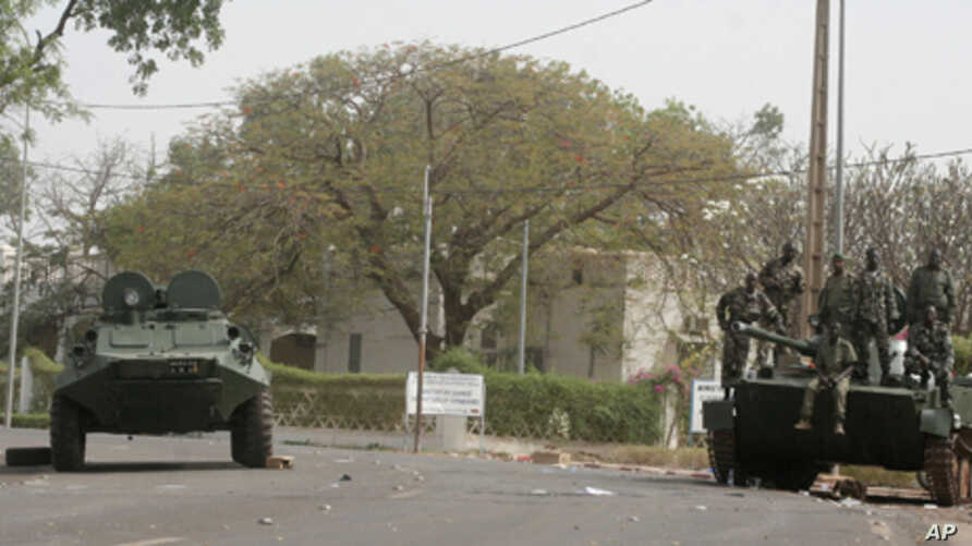 Soldiers secure the area along a road outside the presidential palace after a military coup in Bamako, Mali, Friday March 23, 2012.
