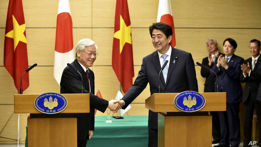 Vietnamese Communist Party General Secretary Nguyen Phu Trong, left, shakes hands with Japan's Prime Minister Shinzo Abe, right, following their joint press announcement at Abe's official residence in Tokyo, Sept. 15, 2015.