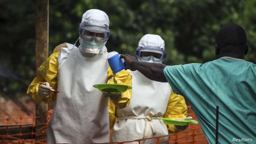 FILE - Medical staff working with Medecins Sans Frontieres (Doctors Without Borders) prepare to take food to patients in the isolation area of an Ebola treatment center in Sierra Leone's Kailahun district, July 20, 2014.