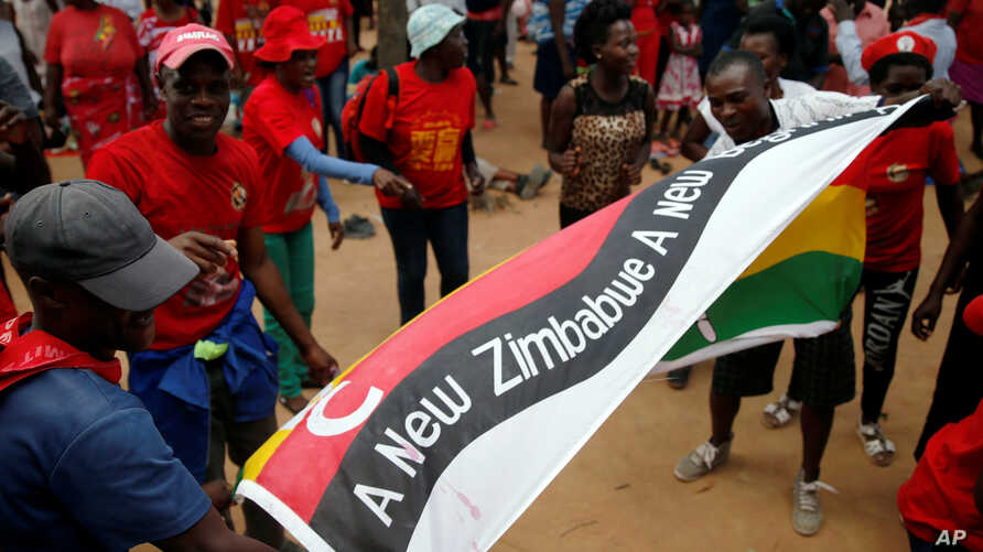 FILE - Opposition Movement for Democratic Cahne (MDC) party supporters wave flags at a rally to launch their election campaign in Harare, Zimbabwe, Jan. 21, 2018.