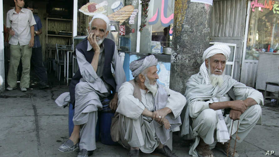 FILE - Former soldiers wait outside a pension office to open in Kabul, Afghanistan, Aug. 26, 2006.