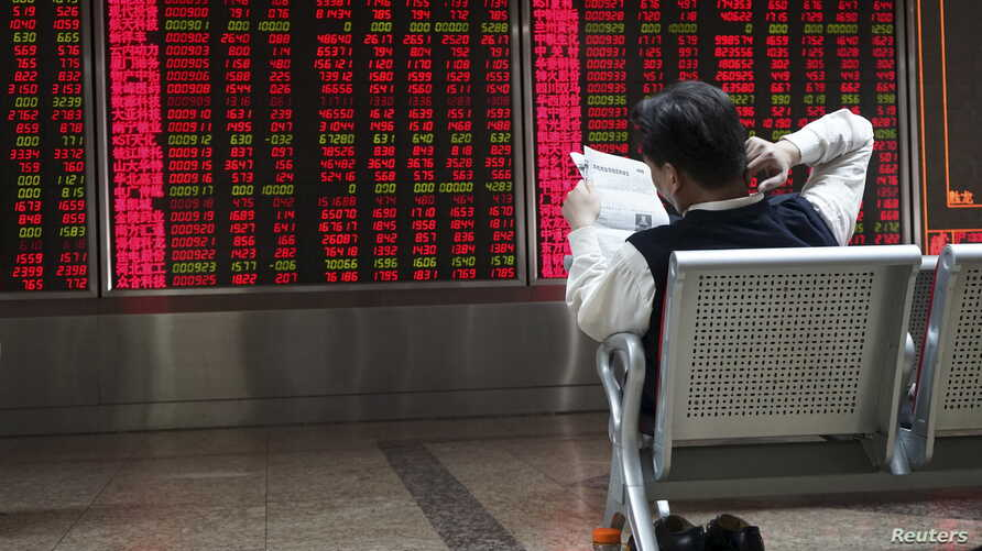 An investor reads a newspaper in front of electronic board showing stock information at a brokerage house in Beijing, China, Oct. 29, 2015.