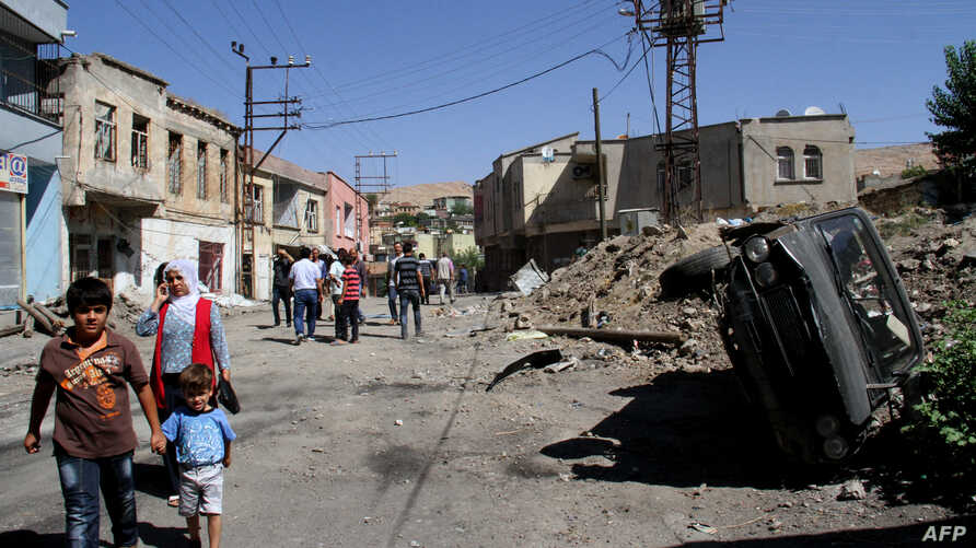 FILE - People walk in a street of Silvan district in Diyarbakir after clashes betweenTurkish army and Kurdish rebels, Aug. 19, 2015.