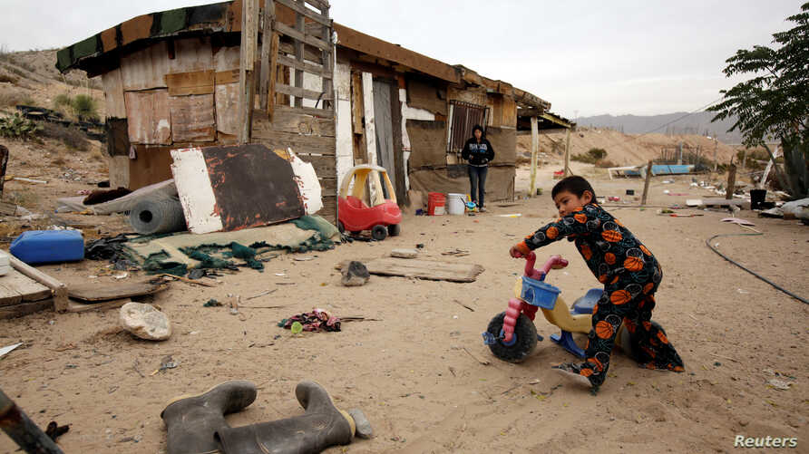 A child plays as his mother looks on outside their house in an impoverished neighborhood in Ciudad Juarez, Dec. 5, 2017. Over 40 percent of Mexicans live below the poverty line.
