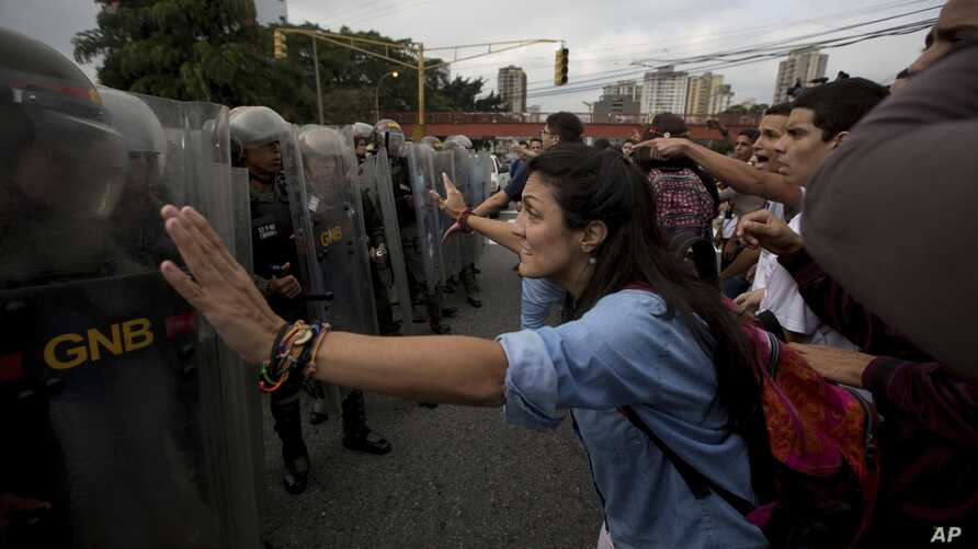 University students confront a line of Venezuelan National Guard officers in riot gear during a protest outside of the Supreme Court in Caracas, Venezuela, March 31, 2017.