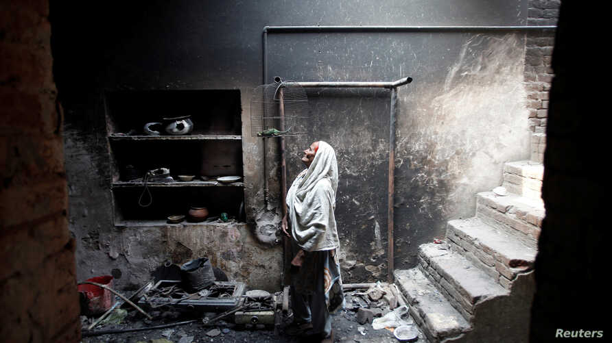 FILE - Azra, 68, looks at her dead pet bird in a cage at her home, which was burnt by a mob two days earlier, in Badami Bagh, Lahore, March 11, 2013.