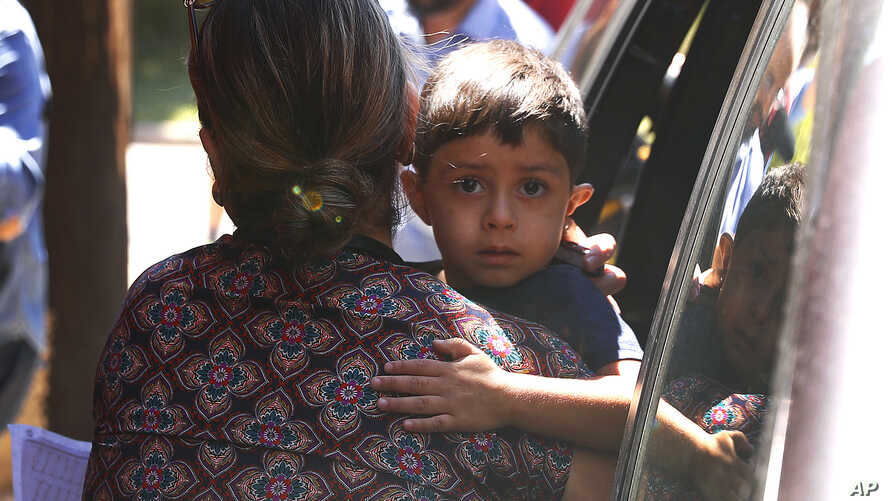 A child from Honduras is brought to the United States Immigration and Customs Enforcement office in Grand Rapids, Mich., July 10, 2018.