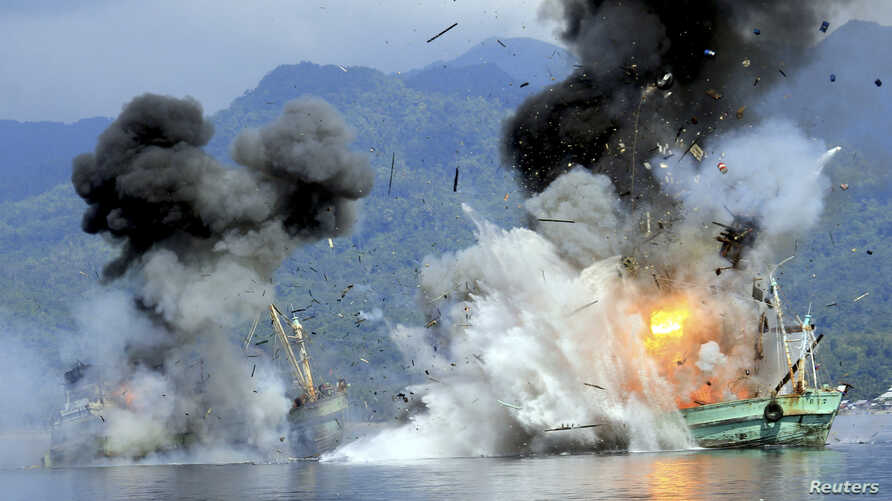 Two foreign-flagged fishing boats registered in Papua New Guinea are destroyed by the Indonesian Navy after they were seized earlier for supposedly illegal fishing off the coast of Ambon, Maluku, Dec. 21, 2014.