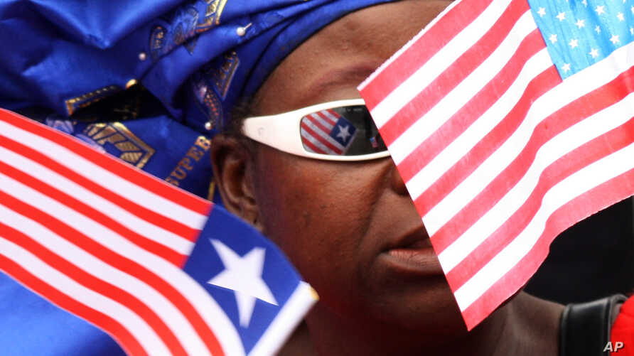 FILE - A market vendor stands among a group of women waving Liberian and American flags to show support for visiting U.S. Secretary of State Hillary Rodham Clinton, in Monrovia, Liberia. Obama recently lifted US sanctions on Liberia.