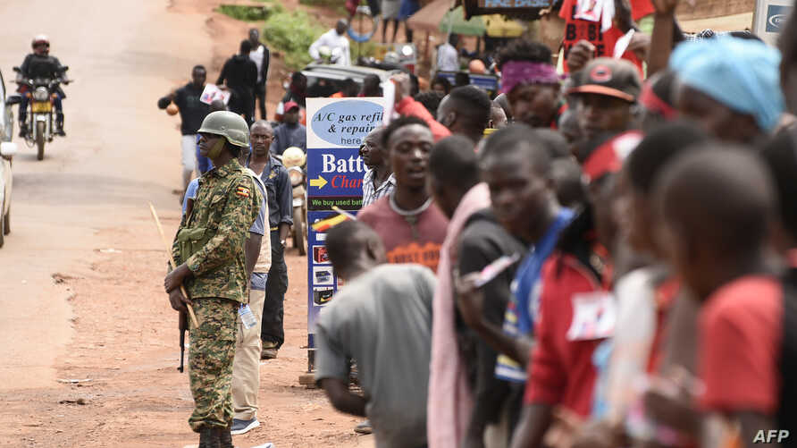 FILE - A Uganda People's Defence Forces (UPDF) soldier stands guard as supporters of Ugandan singer-turned-politician Robert Kyagulanyi, aka Bobi Wine, stand outside of Kyagulanyi's recording studios in Kampala's Kamwokya suburb, Aug. 27, 2018.