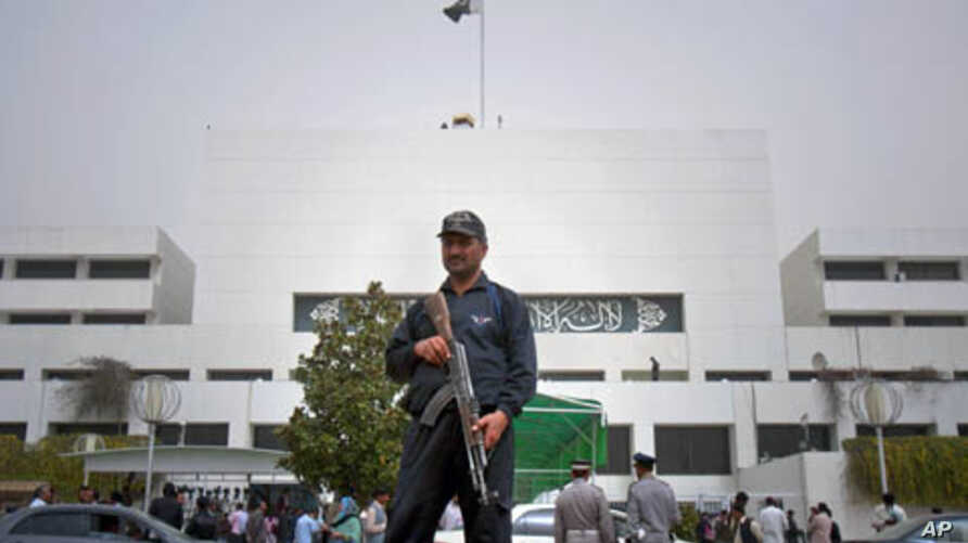 A Pakistani police commando stands guard at the parliament in Islamabad, Pakistan on, March 20, 2012. A special panel met Tuesday to discuss a review of tense relations with the United States.