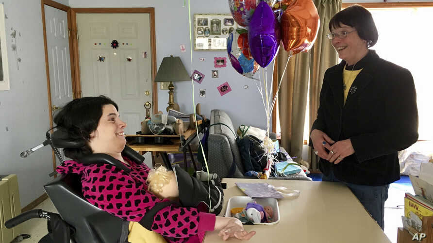 FILE - Stephanie Bushey, right, uses sign language and eye movements to communicate with her daughter, Katie, at their home in West Chazy, N.Y., March 11, 2017. Katie, who lost her vocal and motor skills at birth, relies on assistance from home healt