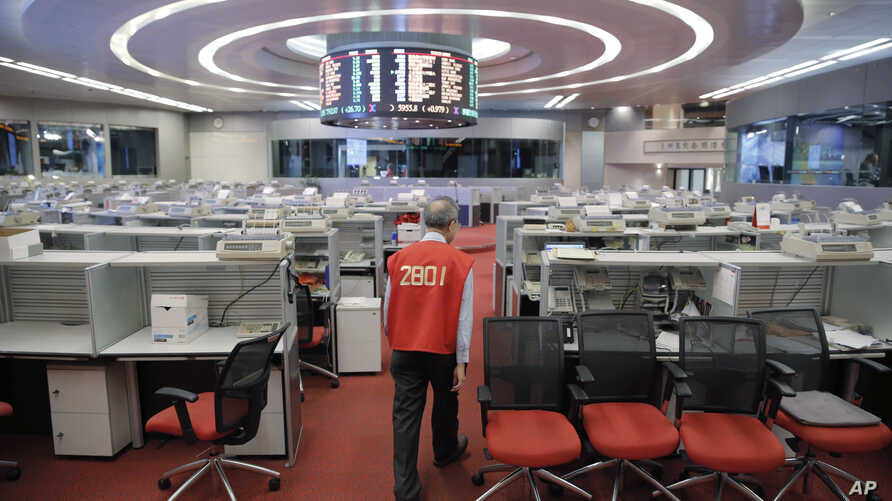 Yip Wing-keung, a trading manager at local brokerage Christfund Securities, wearing his red trading jacket, walks at the Hong Kong Stock Exchange, Oct. 19, 2017.