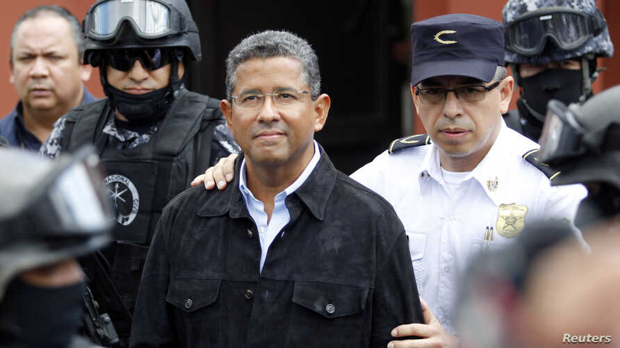 Former El Salvador President Francisco Flores (C) walks out of his house while being guarded by Deputy Director of Police Howard Cotto (R) and the elite unit Reaction Police Group (GRP) in San Benito neigborhood, San Salvador, Sept. 19, 2014.