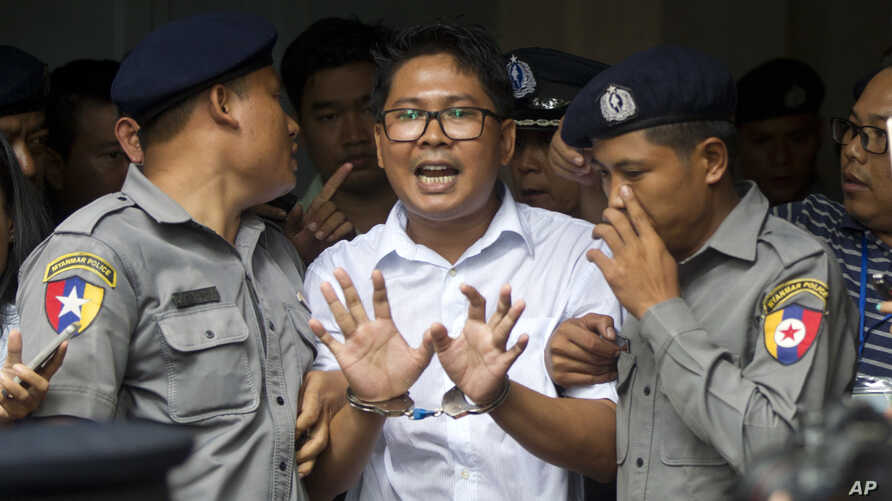 Reuters journalist Wa Lone, center, talks to journalists as he is escorted by police to leave a court in Yangon, Myanmar, Sept. 3, 2018.