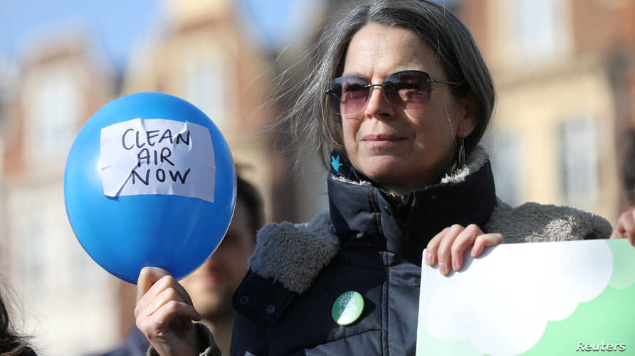 A campaigner holds a balloon at an event organized by the Green Party, demanding air polllution action from the government, in Brixton, London, Feb. 24, 2018.