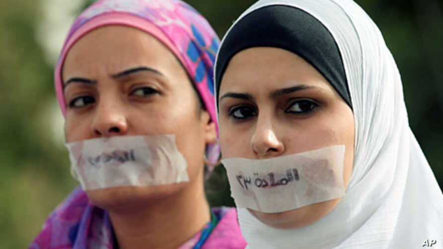 "Jordanian journalists protest in front the Jordanian House of Parliament, with their mouths covered with tape and the words ""article 23,"" in Arabic, against proposed changes to the anti-corruption law they believe will muzzle press freedoms, Amman, S"
