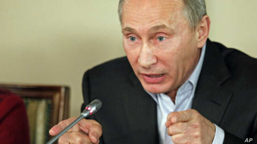 Russian Prime Minister Vladimir Putin talks during a dinner with foreign scholars and journalists at a restaurant on the premises of an equestrian complex outside Moscow, November 11, 2011.