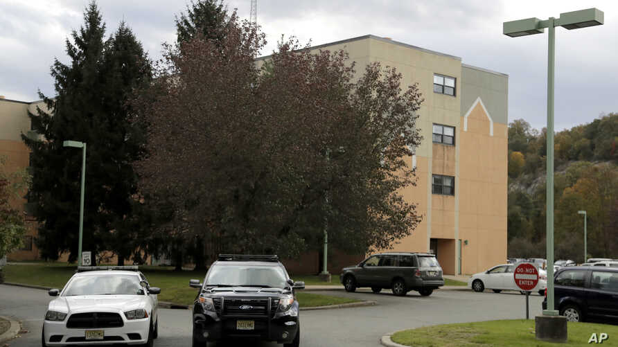 FILE - Police cruisers are parked near the entrance of the Wanaque Center for Nursing And Rehabilitation in Haskell, N.J., where New Jersey health officials have confirmed 28 cases of adenovirus as of Nov. 1, 2018.