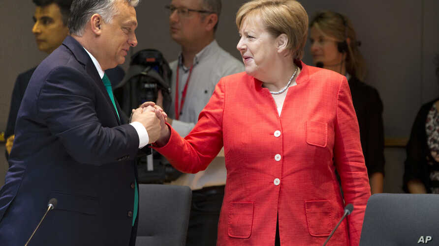 Hungarian Prime Minister Viktor Orban, left, greets German Chancellor Angela Merkel during a breakfast meeting at an EU summit in Brussels, Friday, June 29, 2018.