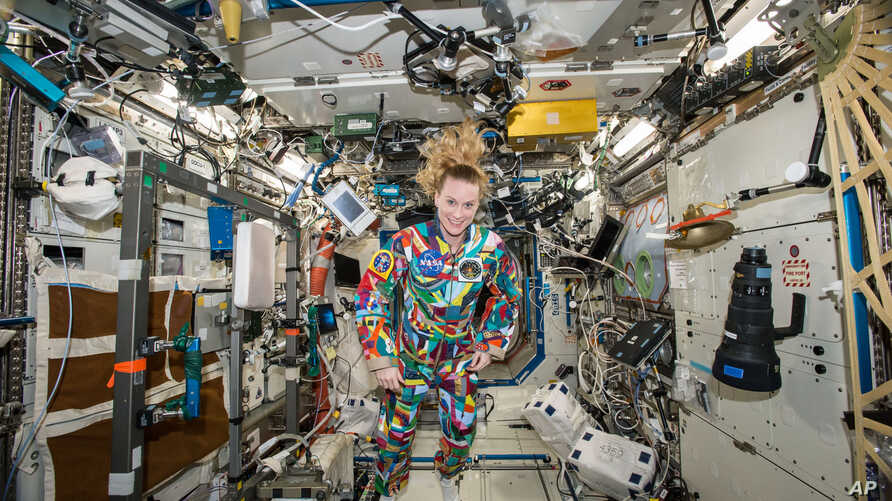 This undated handout photo from NASA shows astronaut Kate Rubins aboard the International Space Station wearing a hand-painted spacesuit decorated by childhood cancer patients at the University of Texas MD Anderson Cancer Center in Houston. NASA said