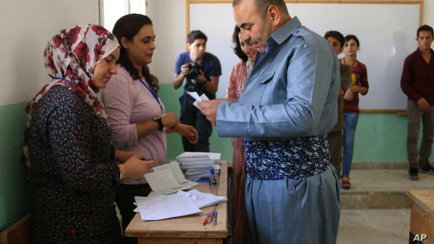In this picture taken on Sept. 22, 2017 and provided by the Press Office of the Kurdish Self-administration Office in Kobani, a Kurdish man, right, reads a paper before he ballots his vote to elected new local councils of the three Kurdish-administer