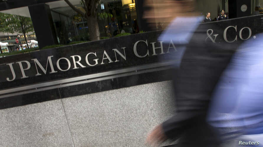 FILE -  People pass the JP Morgan Chase & Co. Corporate headquarters in the Manhattan borough of New York City.