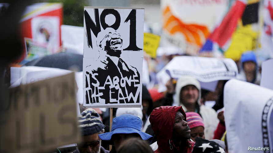 Demonstrators carry placards as they march to protest against corruption in Cape Town, South Africa, Sept. 30, 2015.