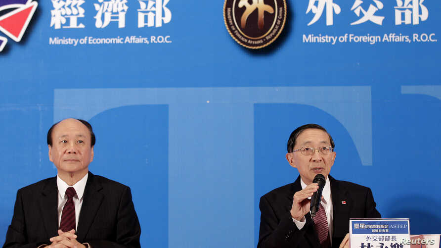 "Taiwan's Economic Affairs Minister Chang Chia-Juch (2nd L) and Foreign Minister David Lin (R) attend a news conference after Taiwan and Singapore signed ""The Agreement between Singapore and the Separate Customs Territory of Taiwan, Penghu, Kinmen and"
