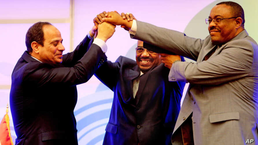 FILE - Sudanese President Omar al-Bashir, center, Egyptian President Abdel-Fattah el-Sissi, left, and Ethiopian Prime Minister Hailemariam Desalegn, right, hold hands after signing an agreement on sharing water from the Nile River, in Khartoum, Sudan
