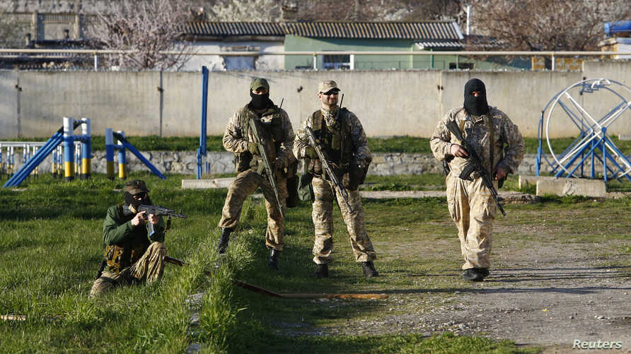 Armed men, believed to be Russian servicemen, stand guard at a military airbase in the Crimean town of Belbek near Sevastopol, Mar. 22, 2014.