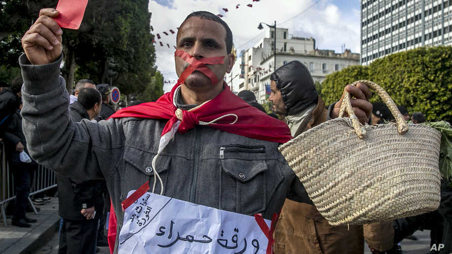 "A gagged Tunisian walks with an empty basket and a red card with a poster reading ""Red card to all politicians without exception"" during a demonstration to mark the eighth anniversary of the democratic uprising in Tunis, Jan.14, 2019."