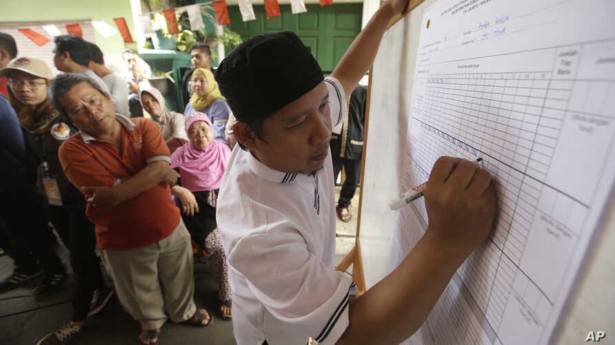 FILE - An electoral worker writes down votes during the gubernatorial election in Jakarta, Indonesia, Feb. 15, 2017.