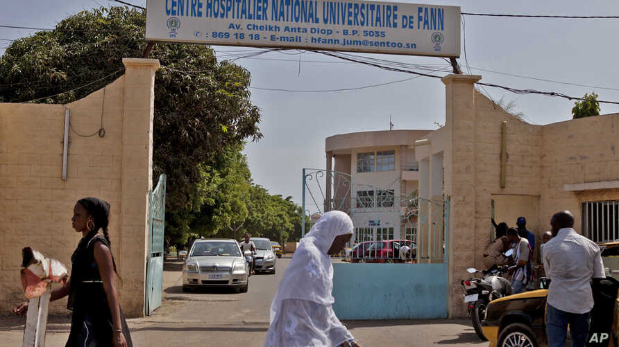 Women walk past the entrance to the  University Hospital Fann, where a man is being treated for symptoms of the Ebola virus in Dakar, Senegal, Aug. 29, 2014.