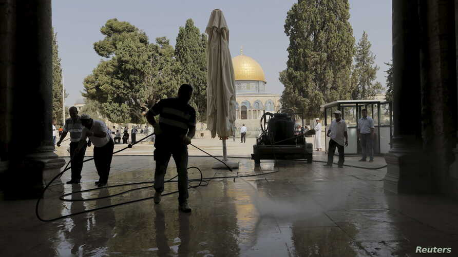 Palestinians clean the Al Aqsa mosque after clashes between Israeli police and Palestinians on the compound known to Muslims as Noble Sanctuary and to Jews as Temple Mount in Jerusalem's Old City,  Sept. 15, 2015.