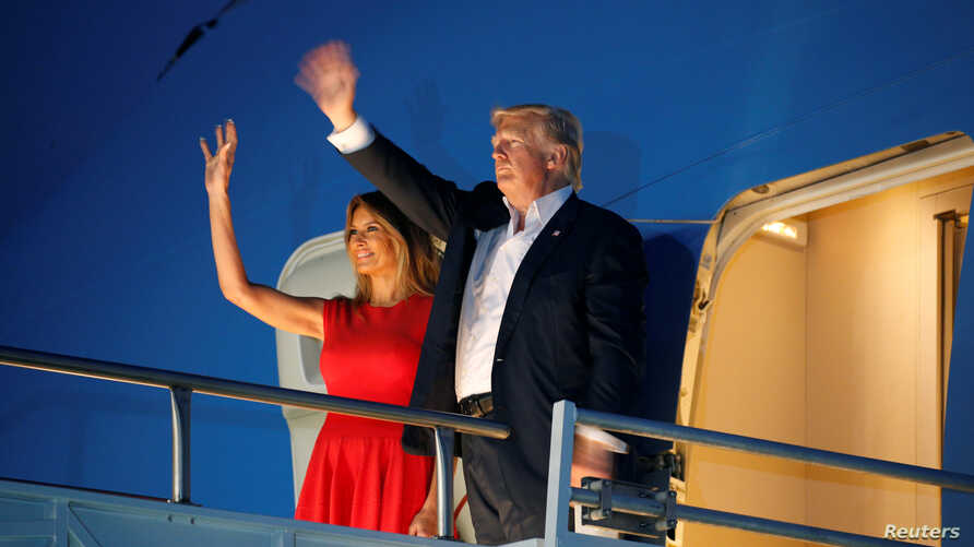 """U.S. President Donald Trump and first lady Melania Trump wave from Air Force One after a """"Make America Great Again"""" rally at Orlando Melbourne International Airport in Melbourne, Florida, Feb. 18, 2017."""