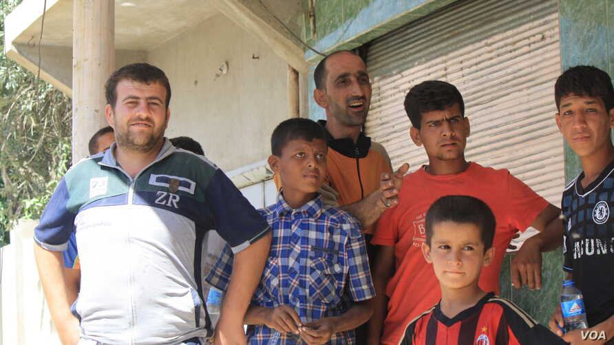 Mohammad Najim, center, asks locals and passers-by for help in the hours after his wife and daughter were lost in the mayhem of hundreds of fleeing families under attack in Mosul, Iraq, June 1, 2017. (H.Murdock/VOA)
