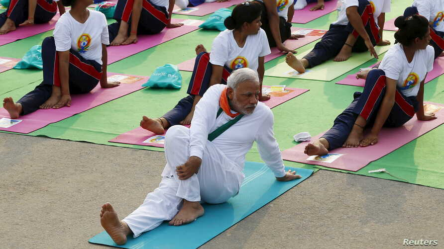 India's Prime Minister Narendra Modi participates in a yoga session to mark International Day of Yoga, in New Delhi, India, June 21, 2015. Modi led tens of thousands of people in the yoga session in the centre of the capital on Sunday to showcase the