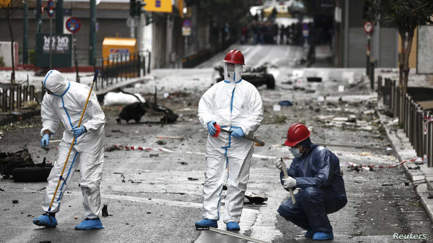 Forensic experts search for evidence on a street where a car bomb went off in Athens, April 10, 2014.