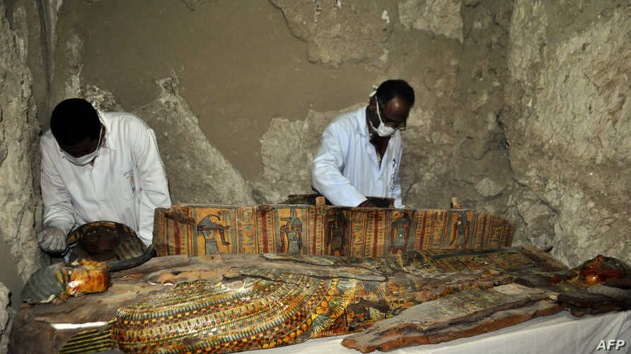 Members of an Egyptian archaeological team work on a wooden coffin discovered in a 3,500-year-old tomb in the Draa Abul Nagaa necropolis, near the southern Egyptian city of Luxor, April 18, 2017.