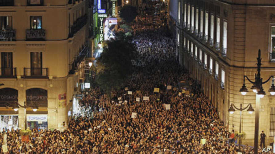 Demonstrators raise their arms just after midnight as they fill up Madrid's Puerta del Sol, spilling into sidestreets,  early May 21, 2011