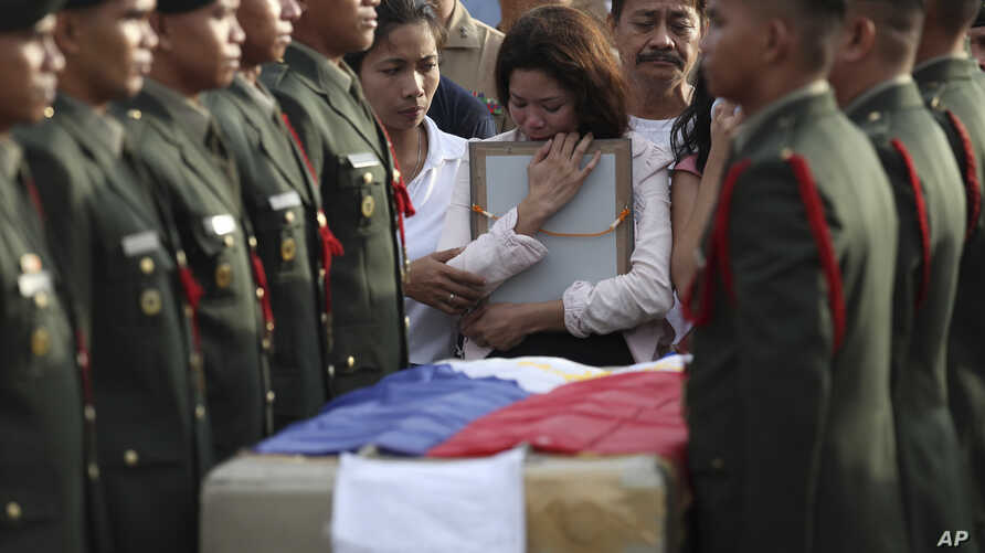 Relatives grieve for a soldier killed while fighting Abu Sayyaf militants in the southern Philippines. Services were at Villamor Air Base near Manila June 21, 2014.