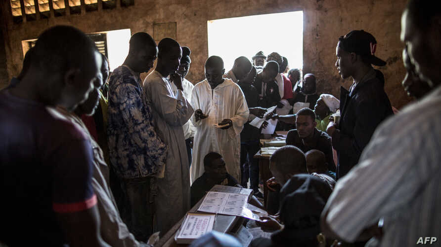 Voters queue to collect their cards at the polling station at the Koudoukou school in the flashpoint PK5 district in Bangui on Dec.14, 2015, where voting operations for the Constitutional Referendum are still underway.