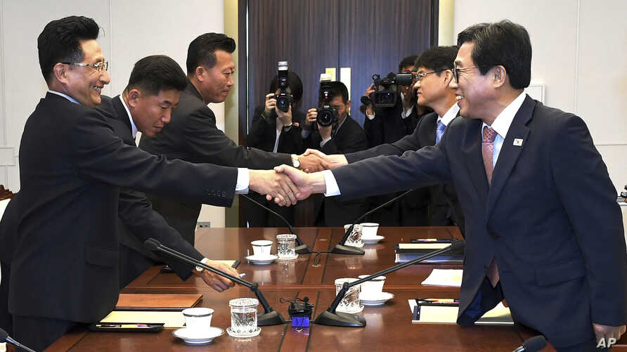 In this photo provided by the South Korea Culture And Sports Ministry, South Korean head delegate Jeon Choong-ryul, right, shakes hands with his North Korean counterpart Won Kil U during a meeting at the southern side of Panmunjom in the Demilitarize