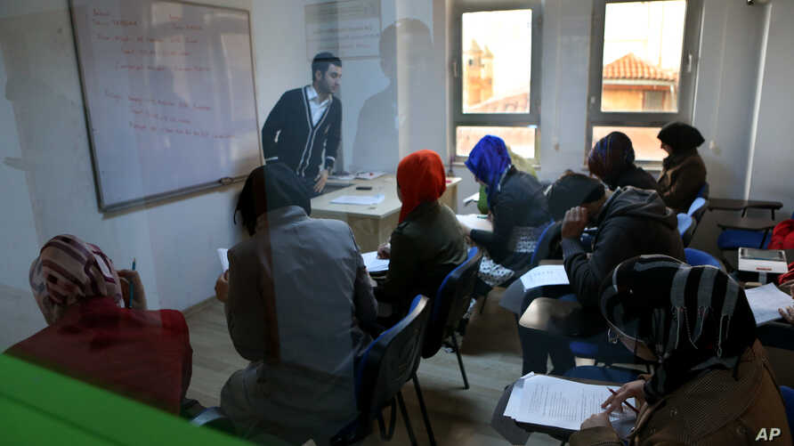 Syrian refugees are seen through a window attending an English language class, at a multi-service center for Syrian refugees in Gaziantep, Turkey, April 22, 2015.
