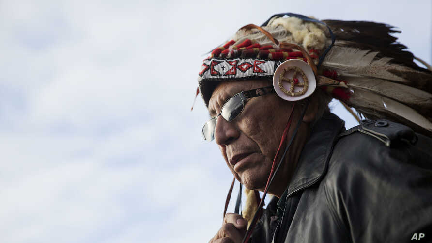 FILE - Chief Arvol Looking Horse, a spiritual leader of the Great Sioux Nation puts on his headdress for an interfaith ceremony at the Oceti Sakowin camp where people have gathered to protest the Dakota Access oil pipeline in Cannon Ball, N.D. As cit